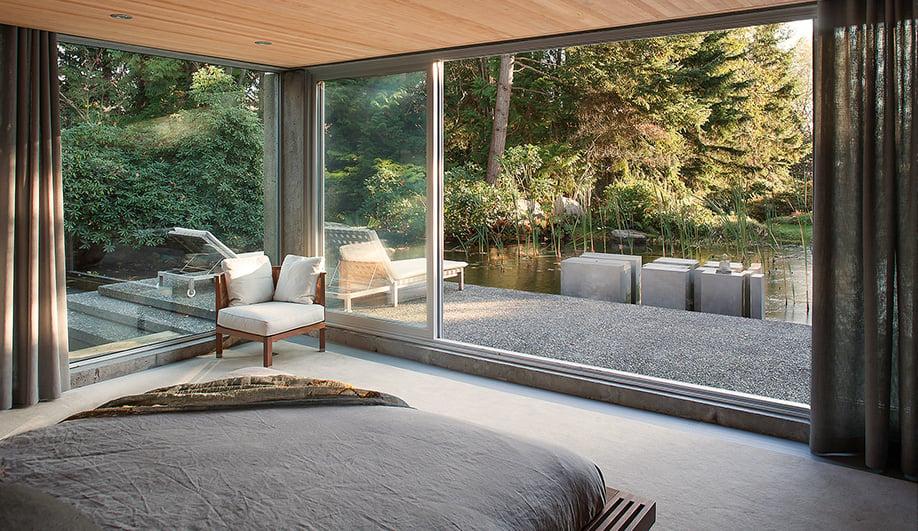 One glazed corner of the master bedroom faces the backyard's lush vegetation.