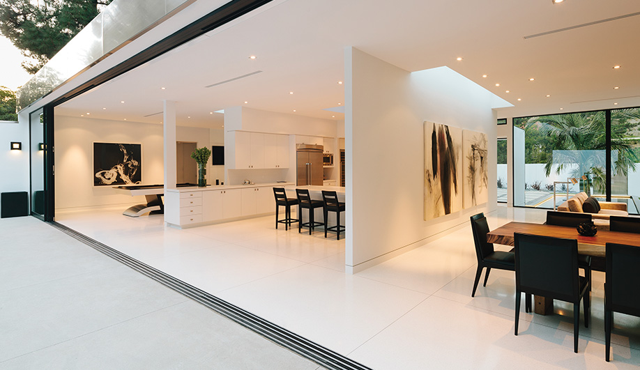 Multi-track glass doors by Fleetwood slide away, removing any barrier between the interior spaces and the courtyard.