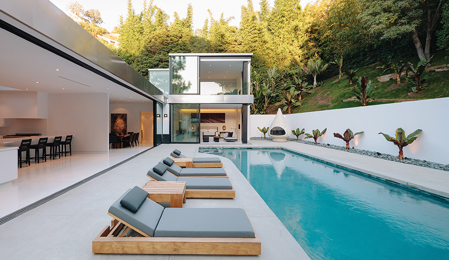 At the centre of the house, aboot-shaped pool with a row of loungers by Marmol Radziner invites relaxation.