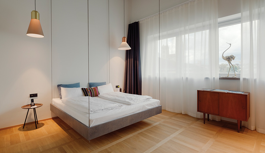 Steel rods mounted from the ceiling allow a custom bed to float in a suite by German musician Michi Beck.