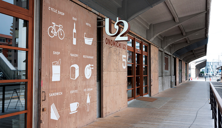 Referencing the Jap­anese word for ware­- house (uwaya), U2 is the second of three revitalized storage buildings on the Onomichi wharf. The massive steel doors of the complex now sport wayfinding graphics.