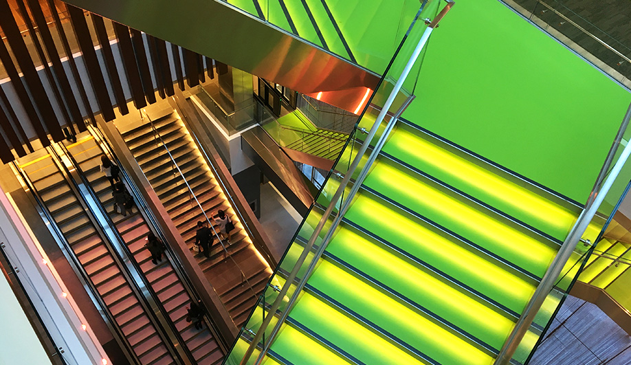 Green stairways illuminated with LED stripes zigzag through the new building's central atrium.
