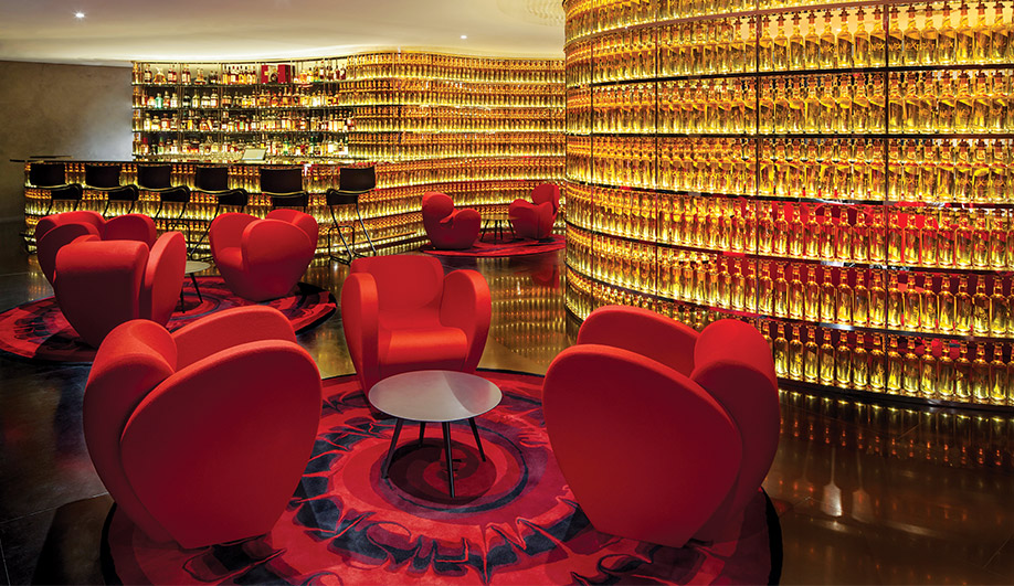 In the Next Whisky Bar, a wraparound wall made of illuminated whisky bottles is complemented by Size Ten loungers – both are designed by Ron Arad, as are the custom rugs manufactured by Nanimarquina.
