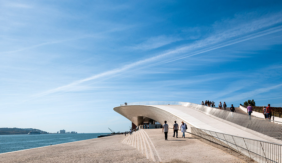 An expansive boulevard along the Tagus River leads to the MAAT's crescent-shaped entrance. Levete's design allows people to walk in, through and on top of the building.