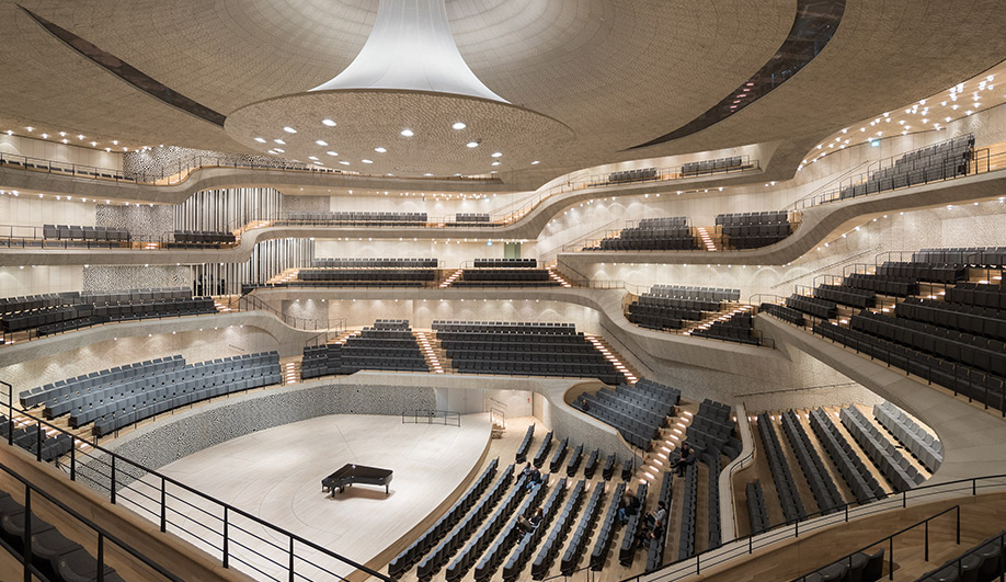 The firm compares the 2,100-seat Grand Hall, with its central peak, to a tent. The ceiling and walls are finished with engineered gypsum fibre panels sculpted into a scalloped pattern that scatters sound waves for superior acoustics. The organ was designed by Johannes Klais Orgelbau of Bonn; some of the largest of the organ's 4,765 pipes (visible at centre-left) are placed where guests can walk alongside, and even touch them. The entire hall is structurally decoupled from the rest of the building for added soundproofing.