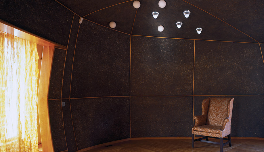 A yurt interior with copper-wire curtains. The walls are made of black clay and chopped straw with oak beading.