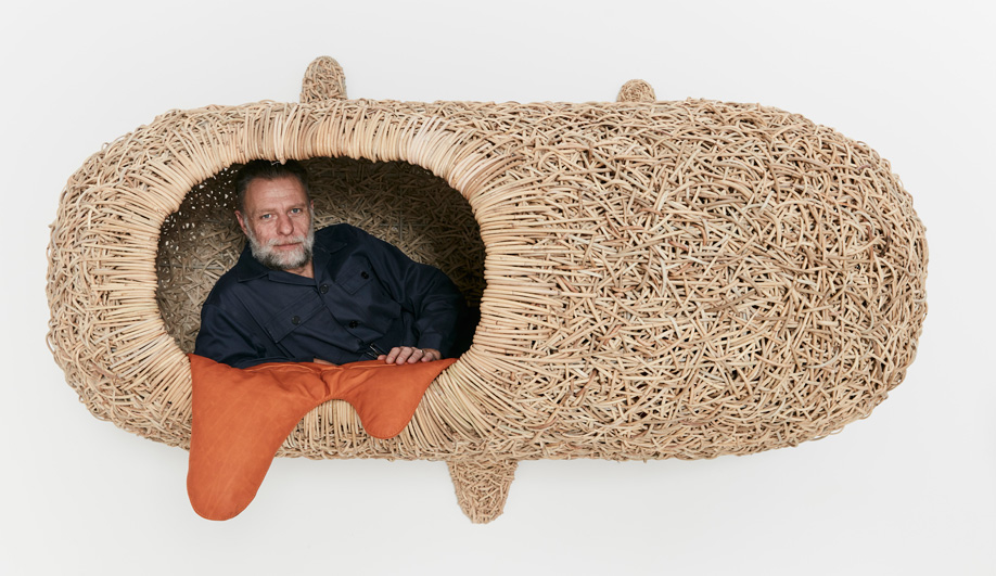 "Porky Hefer reclines in one of his wall-mounted, human-size ""nests"" woven from kubu cane."