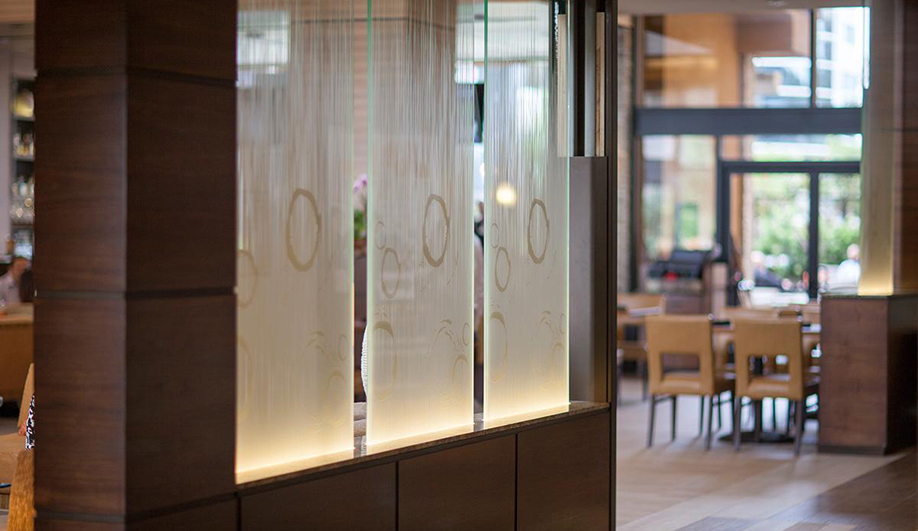 Forms+Surfaces glass: ViviGraphix Gradiance glass with custom graphics adds an elegant touch to this upscale hotel restaurant without compromising the natural daylight or open-air atmosphere of the space.