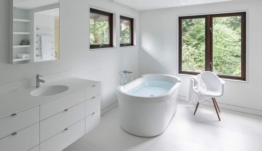 White Corian reflects the greenery outside in this bathroom developed by Gates-Suter Architects.
