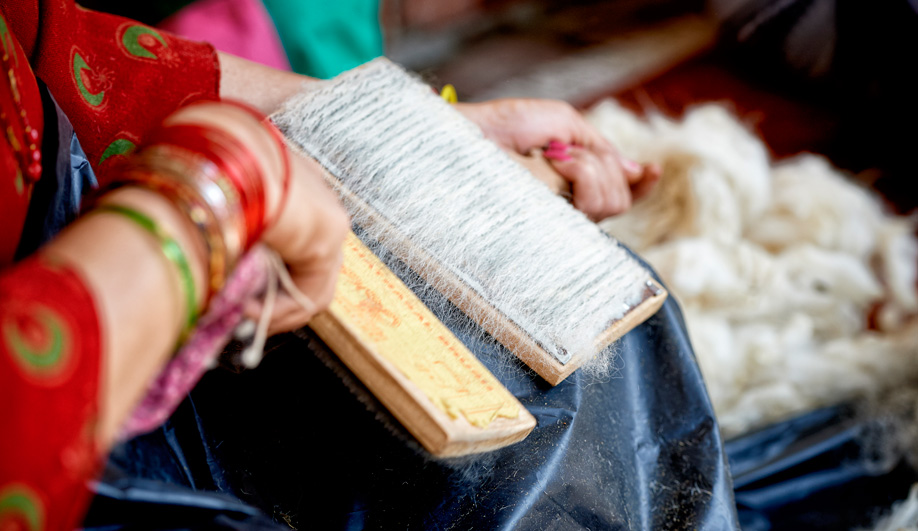 Before the weaving process begins, wool is carded to blend the fibres. Jan Kath