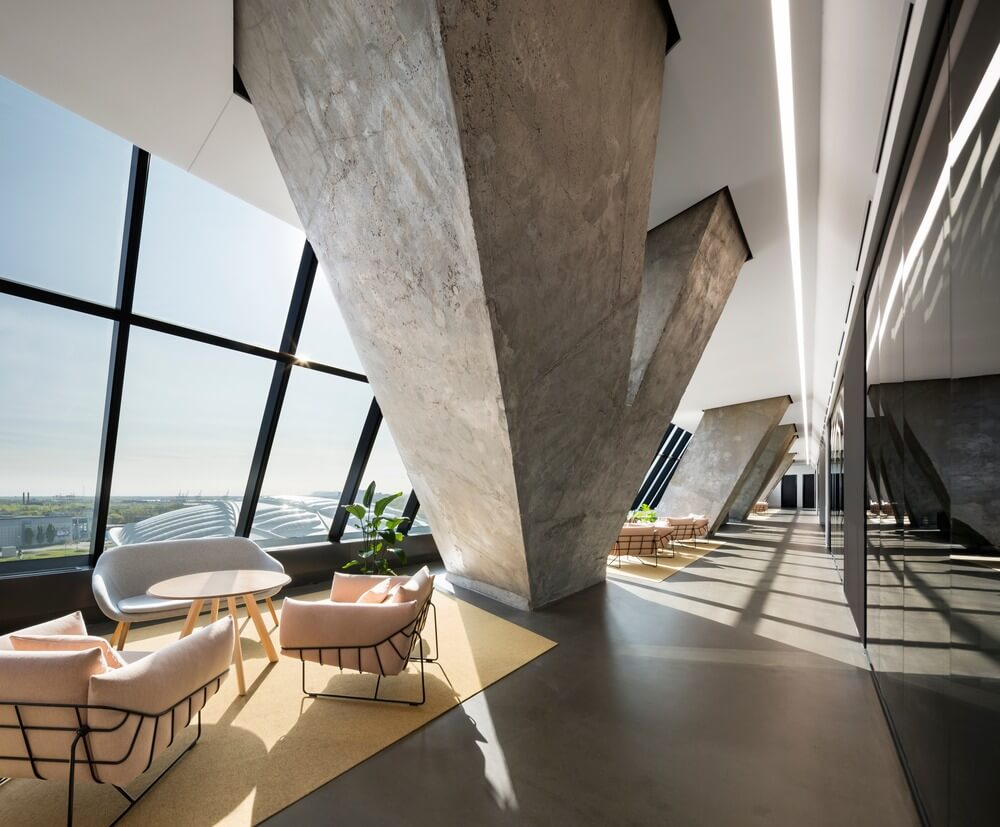 The office perimeter is defined by the tower's slanted concrete structural shell