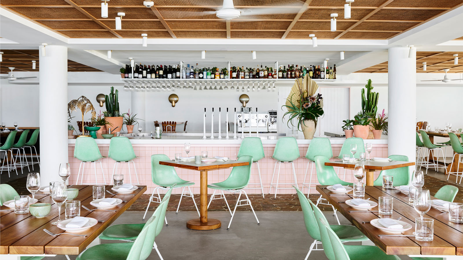 Tropical Restaurant and Bar. Pistachio coloured chairs with wooden tables and bar with pink tiles.