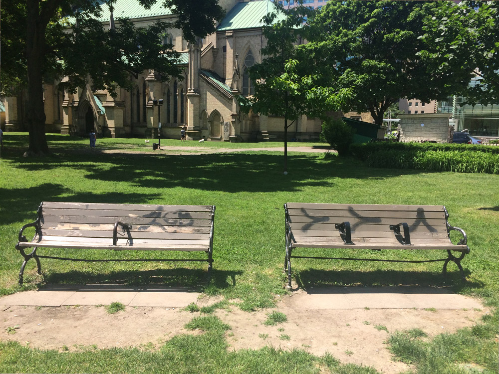 Two benches in a park, both with armrest dividers