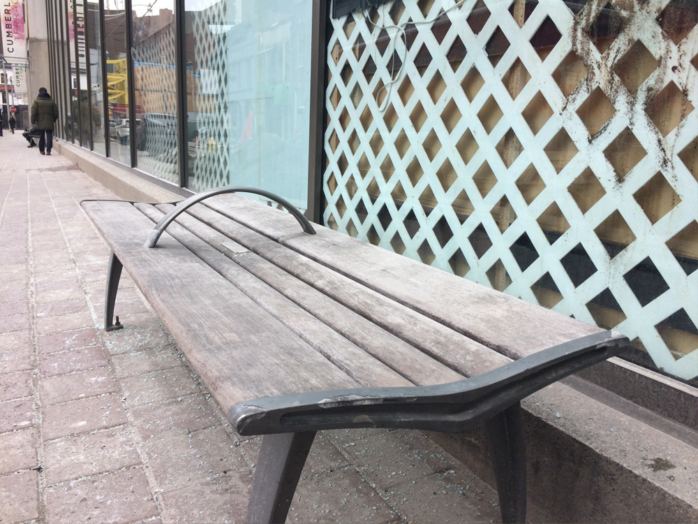 Bench on the sidewalk, with curved armrest divider in centre