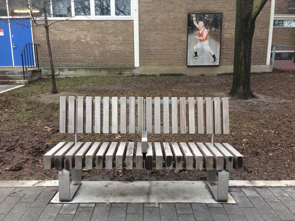 Bench on sidewalk, with armrest divider in centre