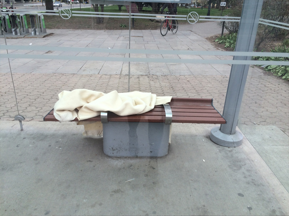 Bench by a bus stop, with a blanket on the seat