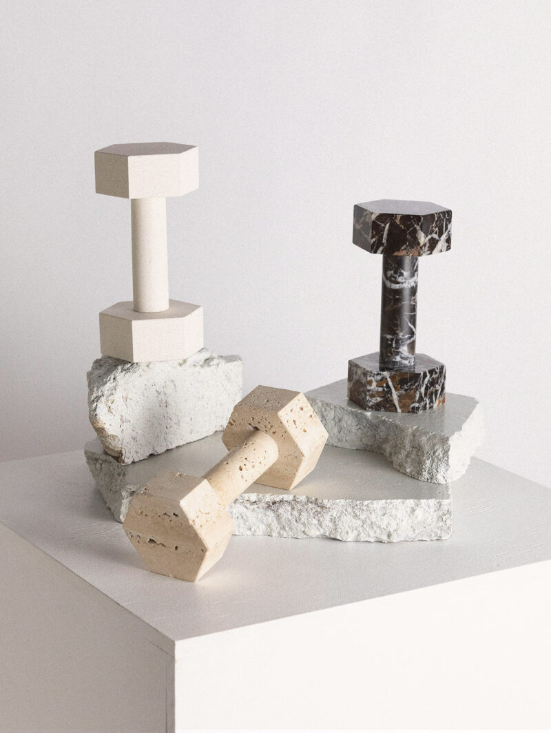 Three dumbbells are arranged on stone pieces.