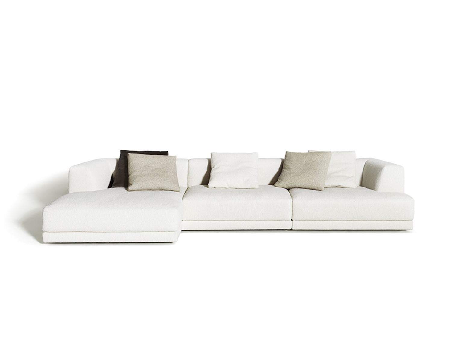 White Alberese sectional chaise with throw pillows in various neutral colours on white background