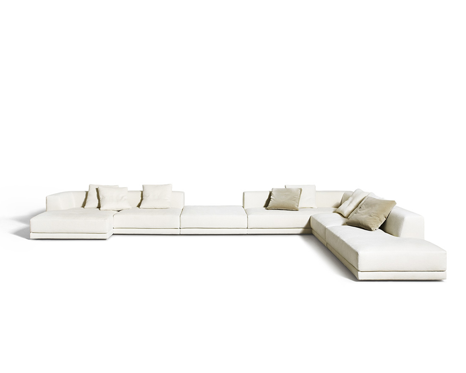 White Alberese modular sectional with throw pillows in various neutral colours on white background