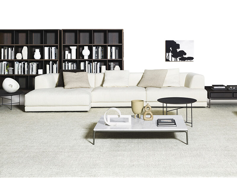 White Alberese sectional chaise on a grey carpet in front of a brown bookcase