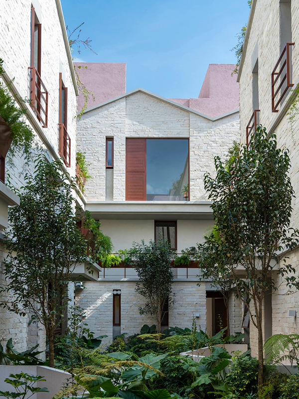 View of the building's courtyard, showing the lush greenery and pink roof volumes behind.