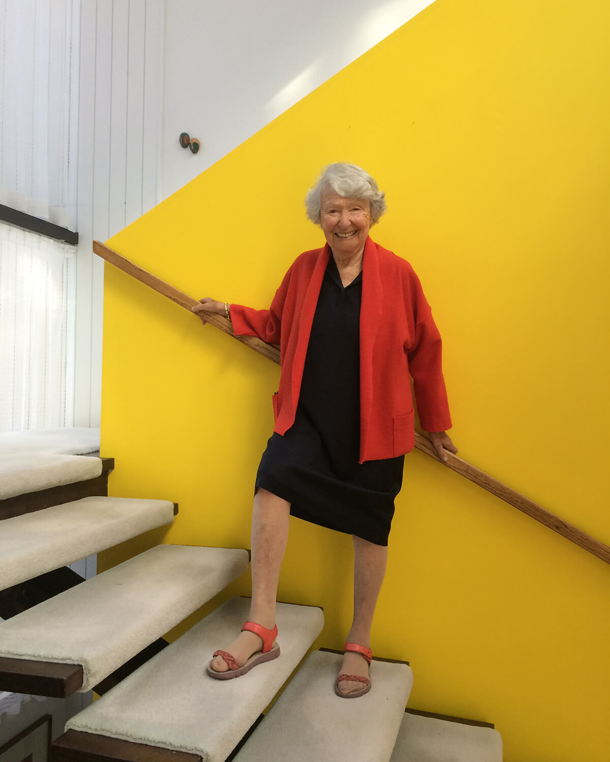 Cornelia Oberlander standing on a staircase in front of a yellow wall