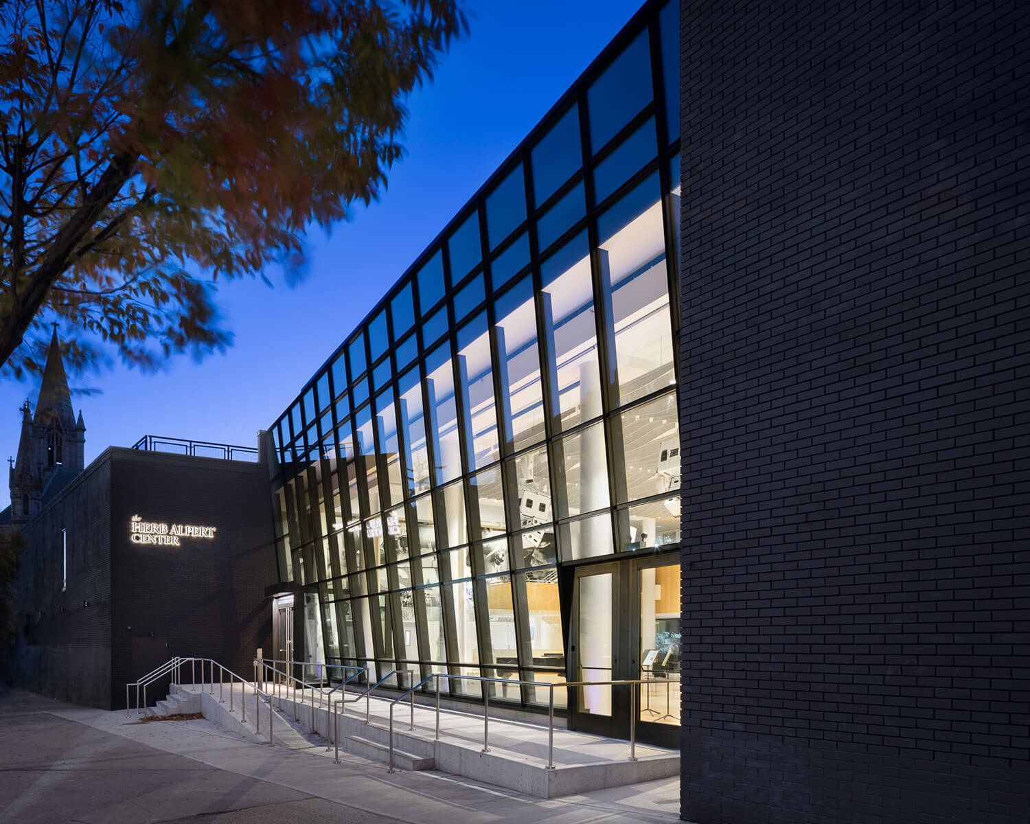 Harlem School of the Arts at night as seen from the street, showing the newly renovated glass facade and accessible entrance ramp