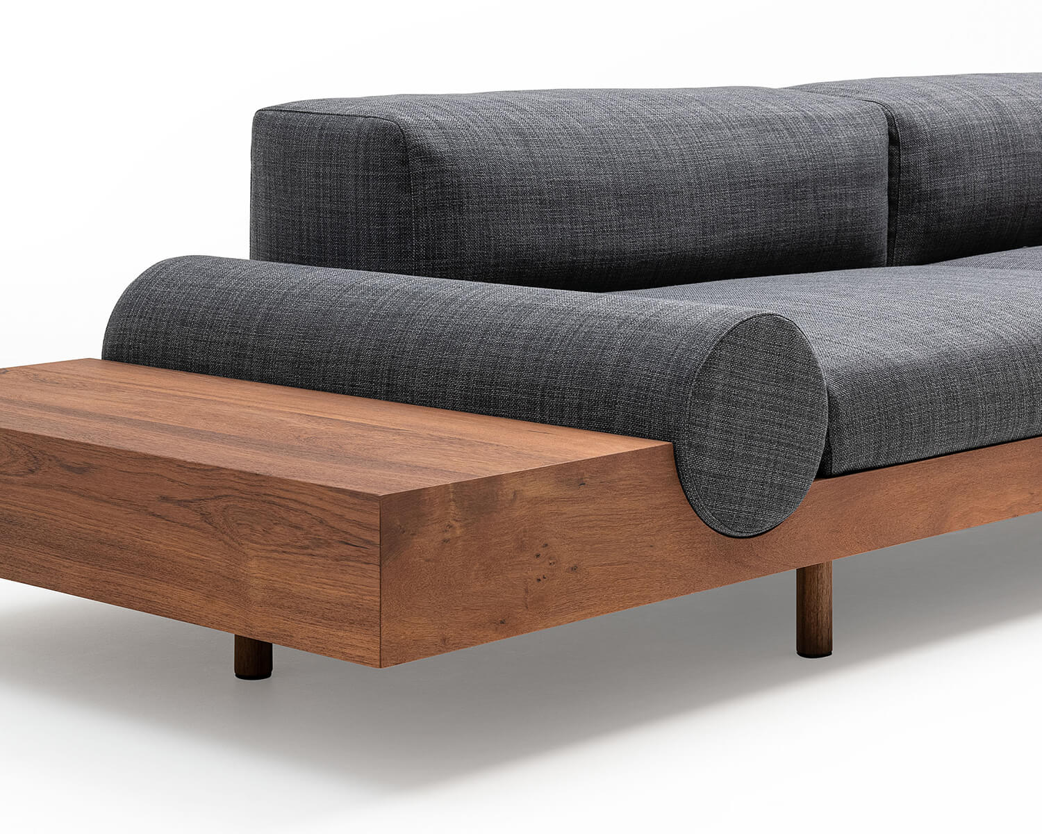 Close-up view of Kasbah modular sectional chaise in grey fabric showing the bolster cushion and teak platform