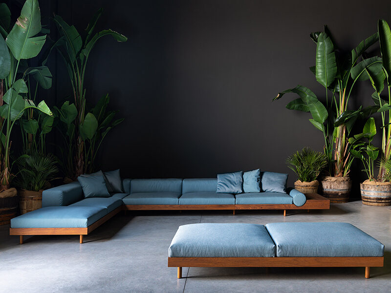 Kasbah modular sectional and chaise lounge in front of a black wall and tall plants