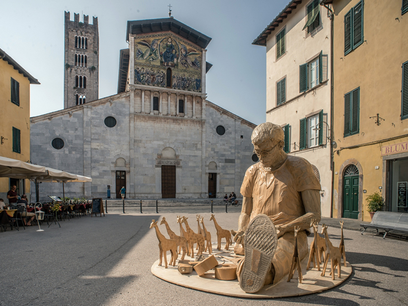 Sculpture of man and small giraffes on the street in Italy