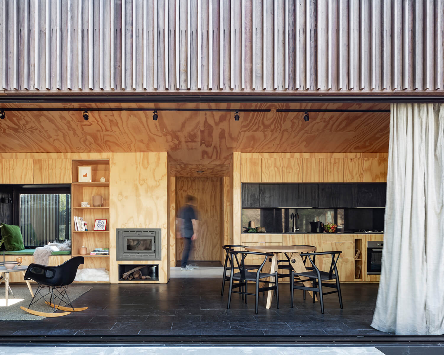 Exterior view of the cabin with the sliding glass doors open, showing the open concept living-dining area