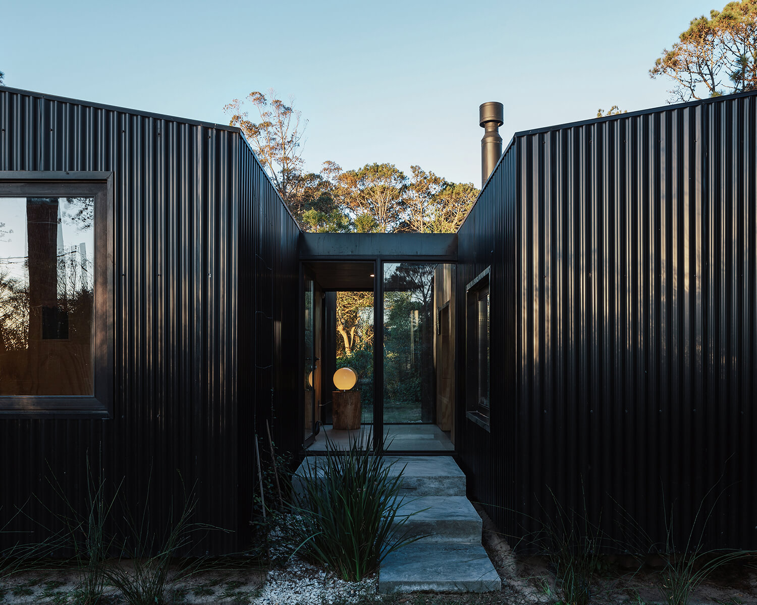 Exterior view of the cabin, showing the glazed walkway and corrugated sheet metal facade