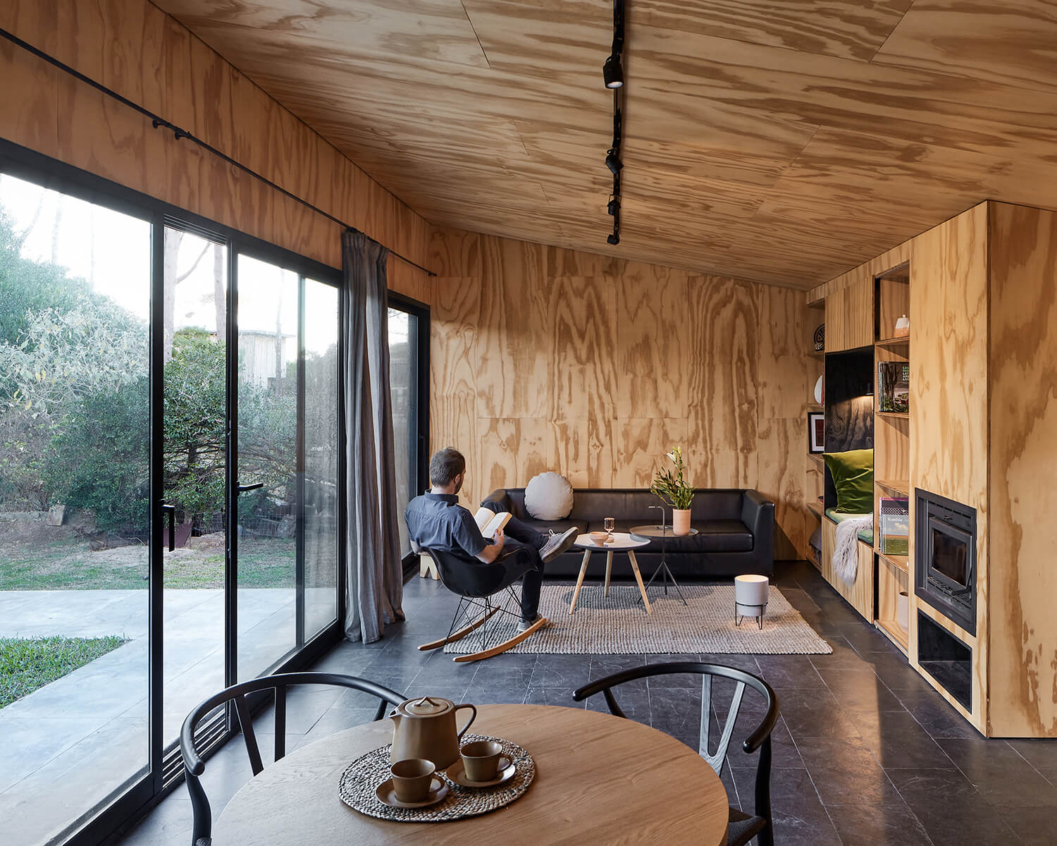 Interior view of the cabin's open concept living-dining area, showing the wood-clad ceiling and walls and black accents