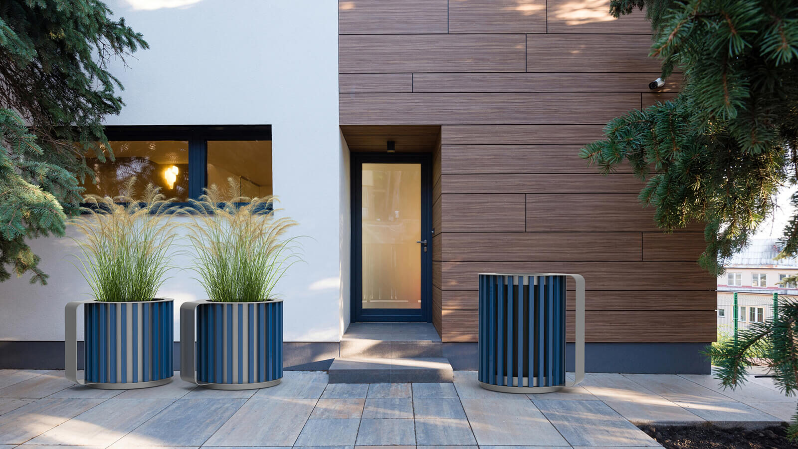 Navy blue Mug planters and garbage bin in front of a white and wood building