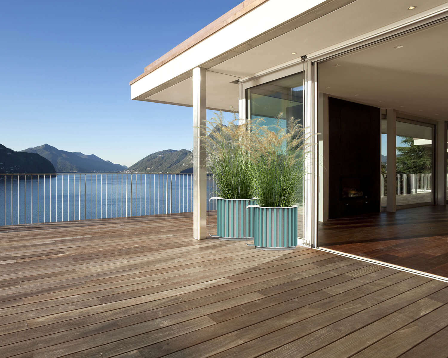 Teal Mug planters on a wooden deck overlooking the water and mountains
