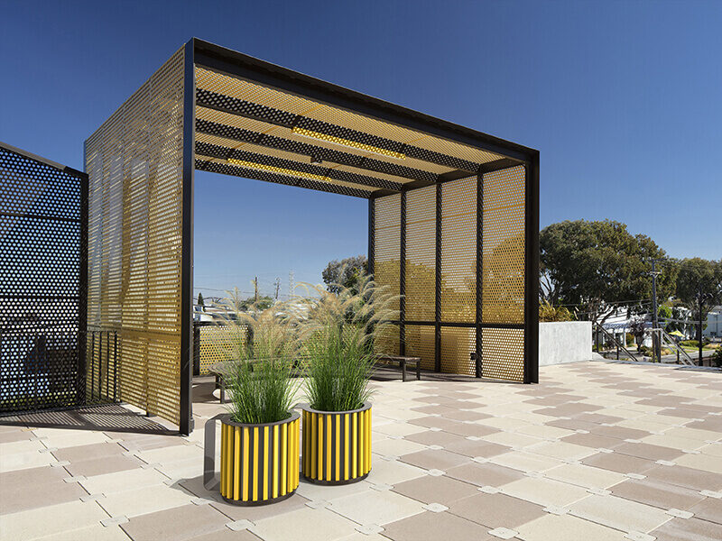 Yellow Mug planters in front of a yellow shade structure