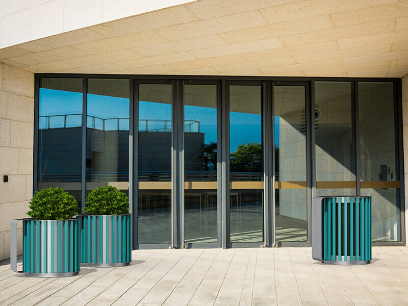 Teal Mug planters and garbage bin in front of a glazed building entrance