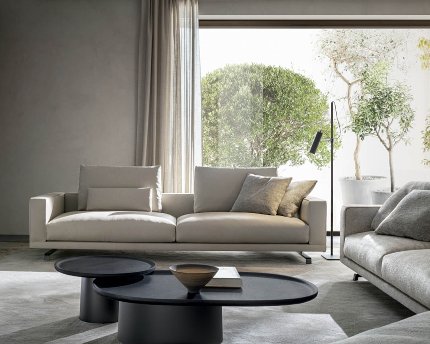 Beige Octave two-seater sofa in front of a window, with round black coffee tables