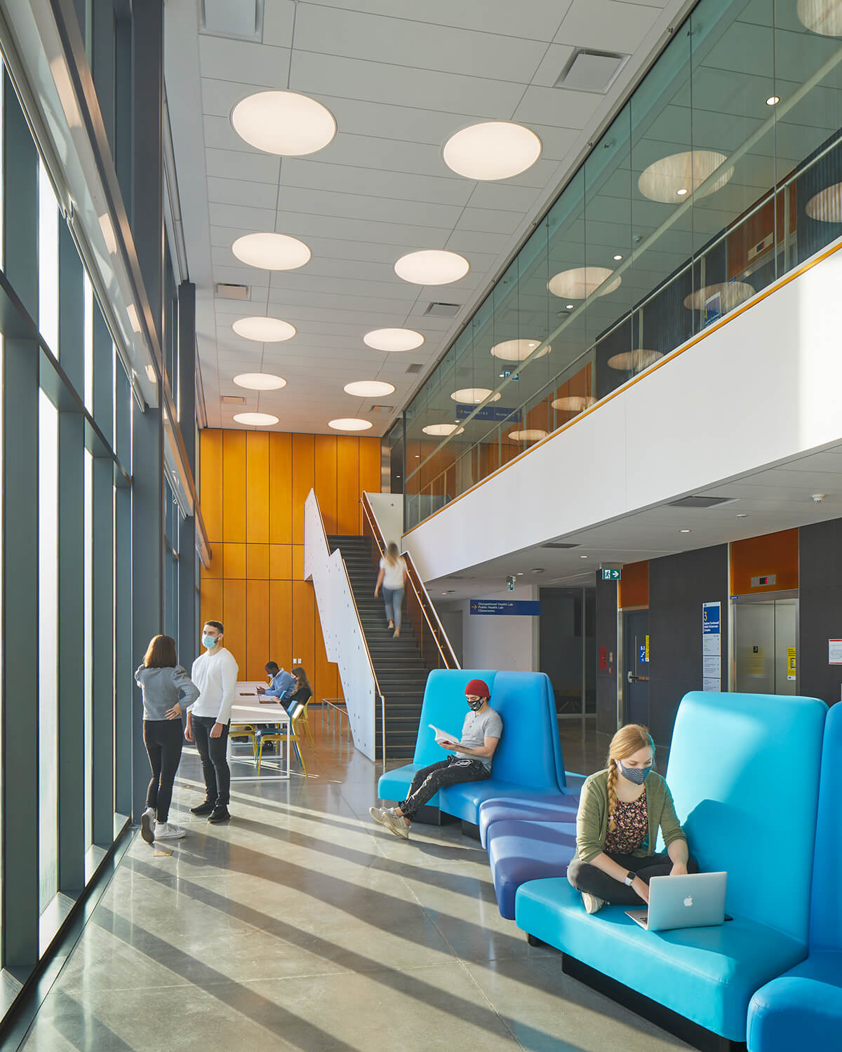 One of building's open seating spaces, showing the staircase and playful blue lounge seating.