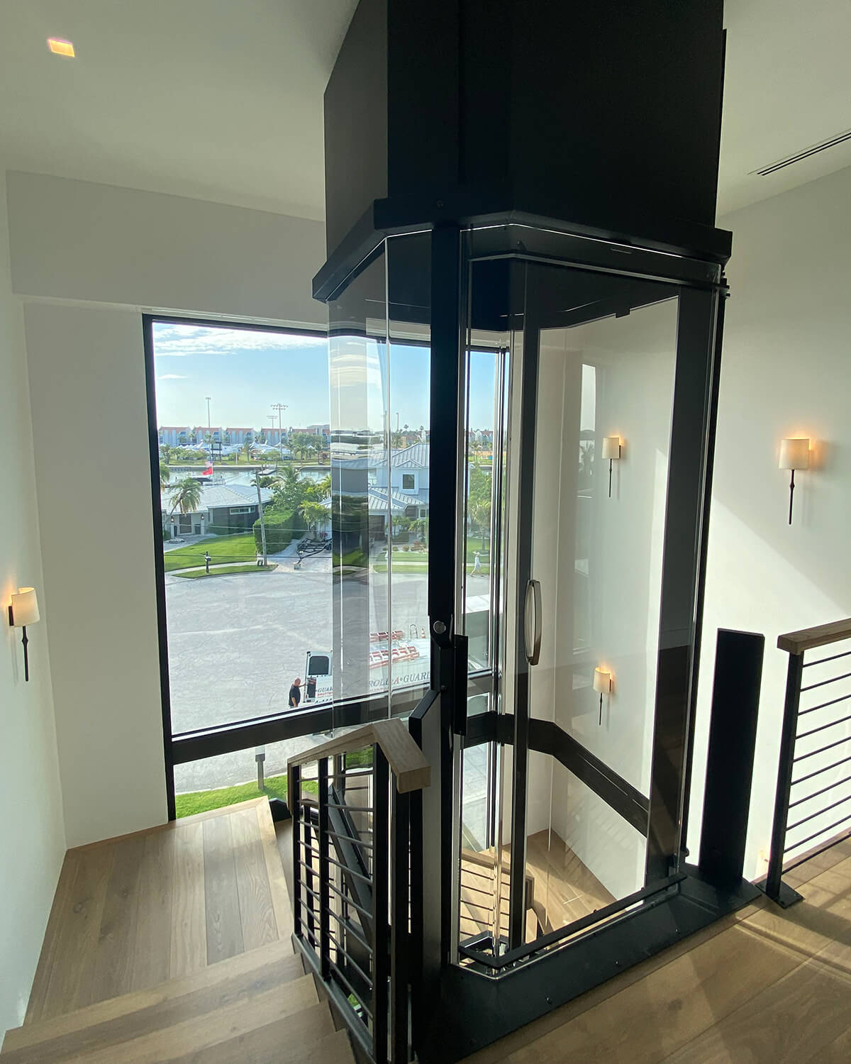 Savaria Octagonal Acrylic Panoramic Home Elevator with black frame opening at top of wooden staircase