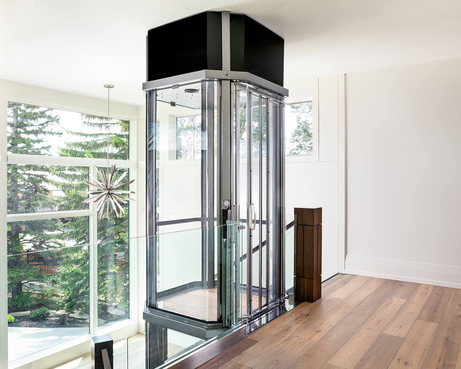 Savaria Octagonal Acrylic Panoramic Home Elevator with silver metal frame opening to wood floor balcony