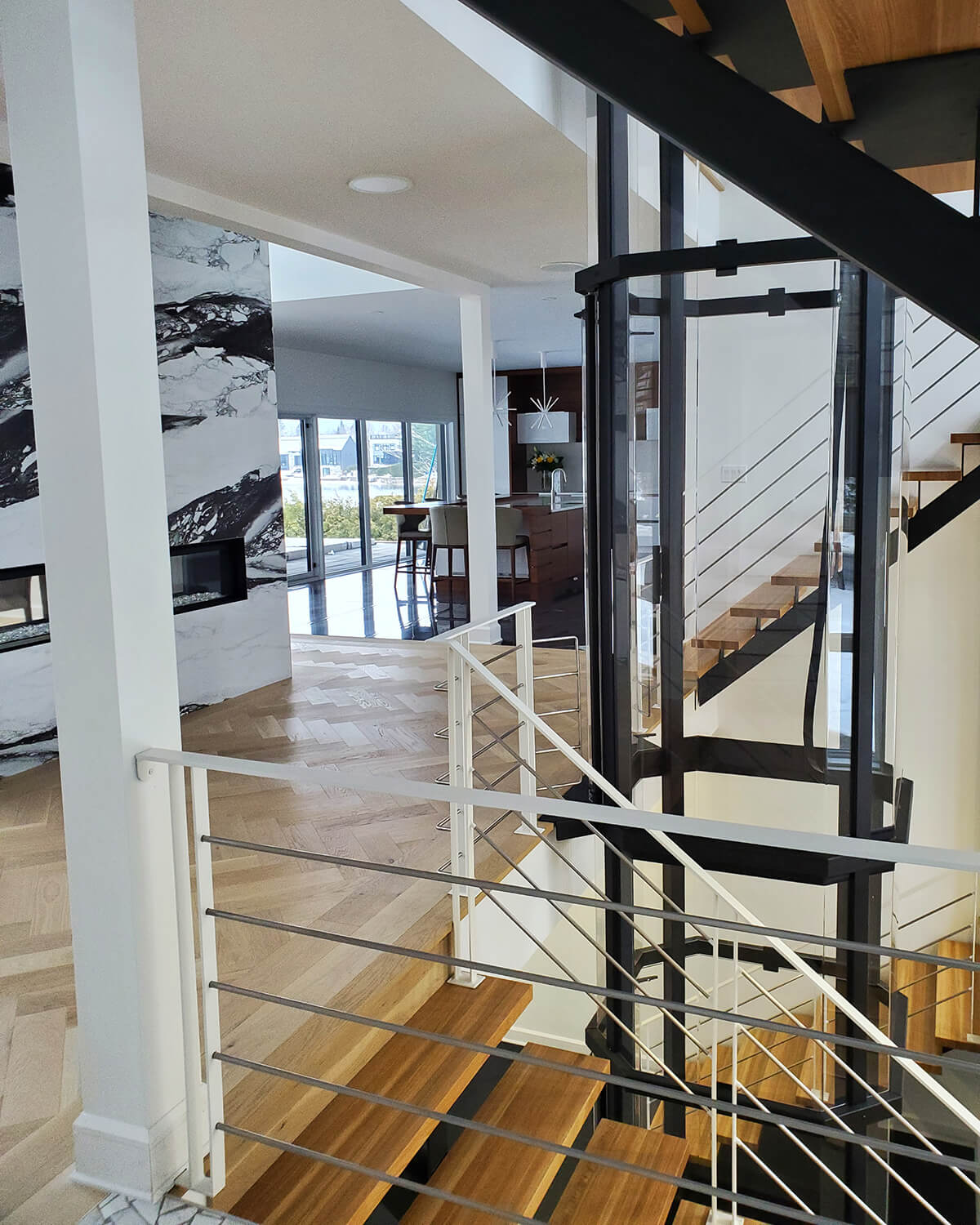 Savaria Octagonal Acrylic Panoramic Home Elevator with black frame between two wooden staircases, as seen from the back