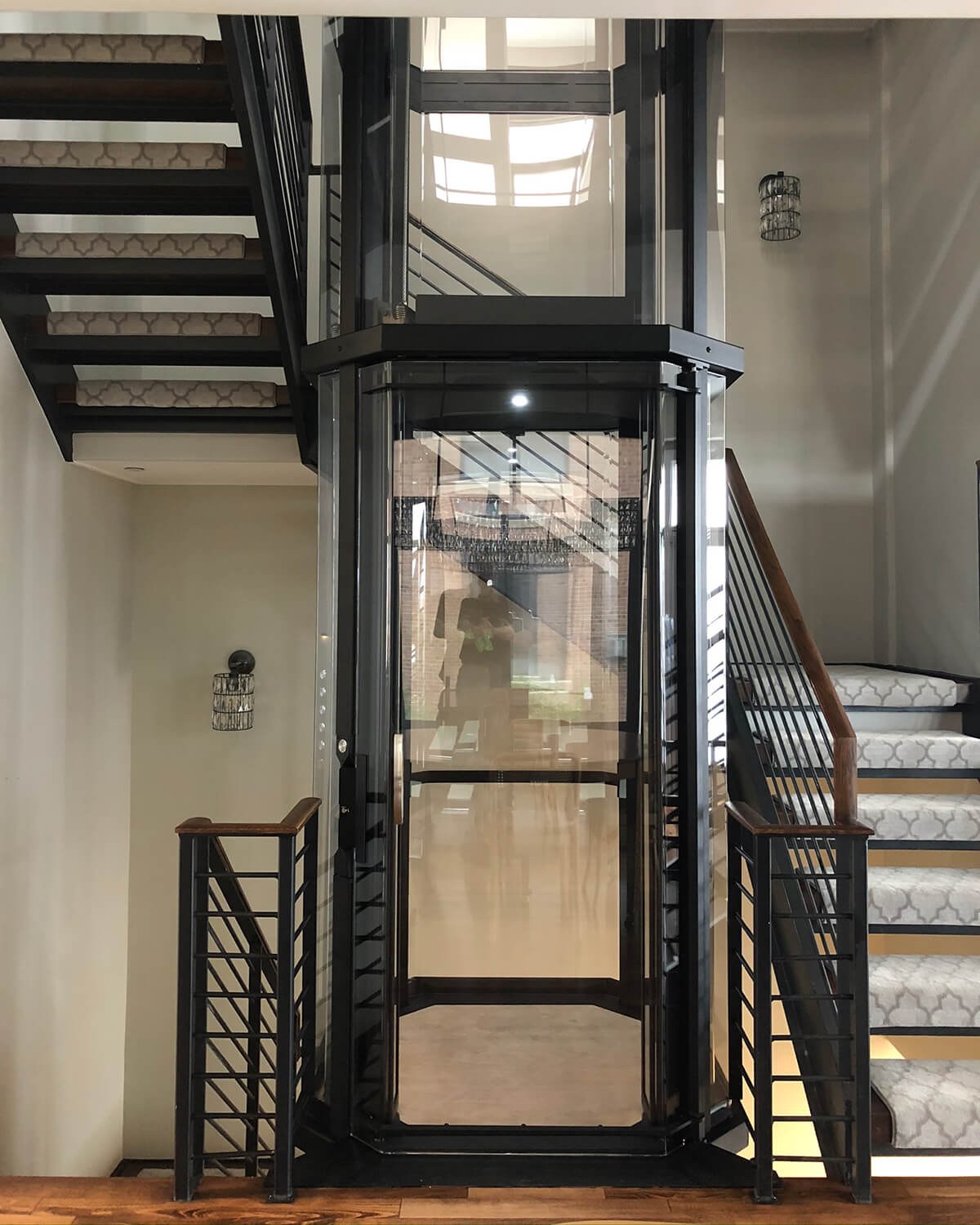 Savaria Octagonal Acrylic Panoramic Home Elevator with black frame installed inside carpeted staircase
