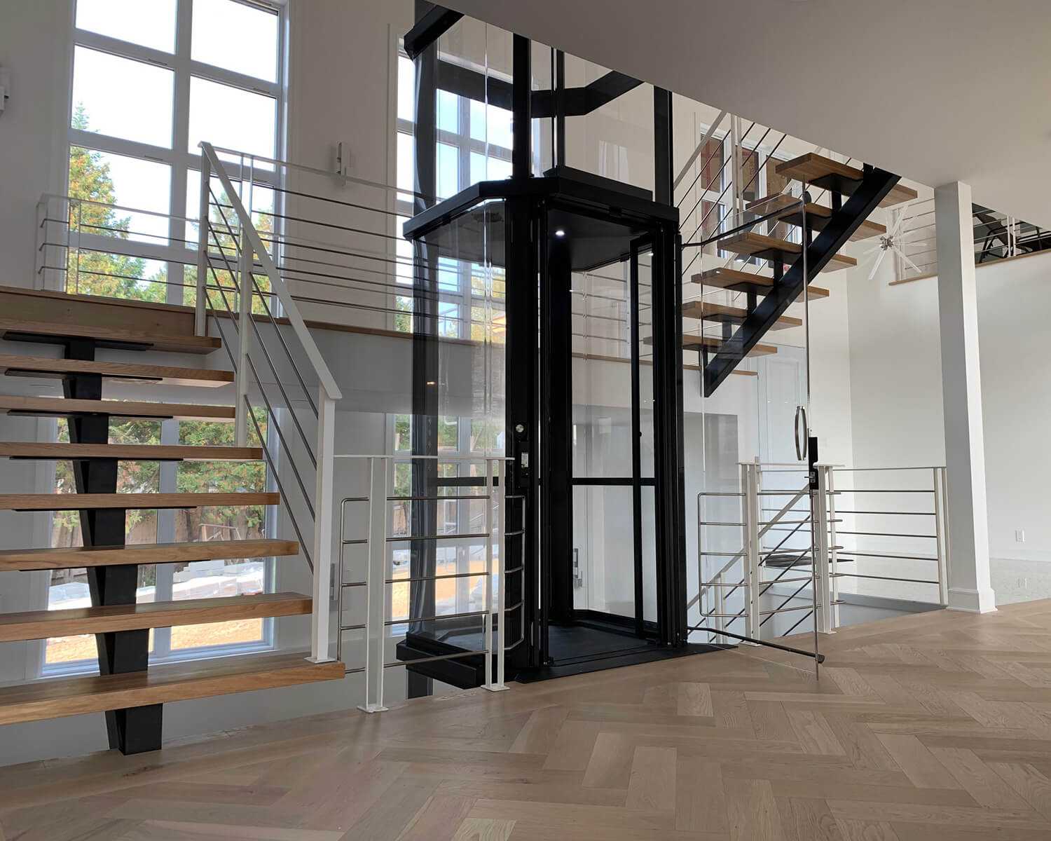 Savaria Octagonal Acrylic Panoramic Home Elevator with black frame between two wooden staircases