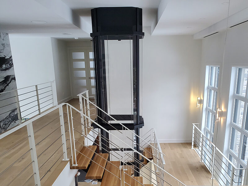 Savaria Octagonal Acrylic Panoramic Home Elevator with black frame between two wooden staircases with white railings