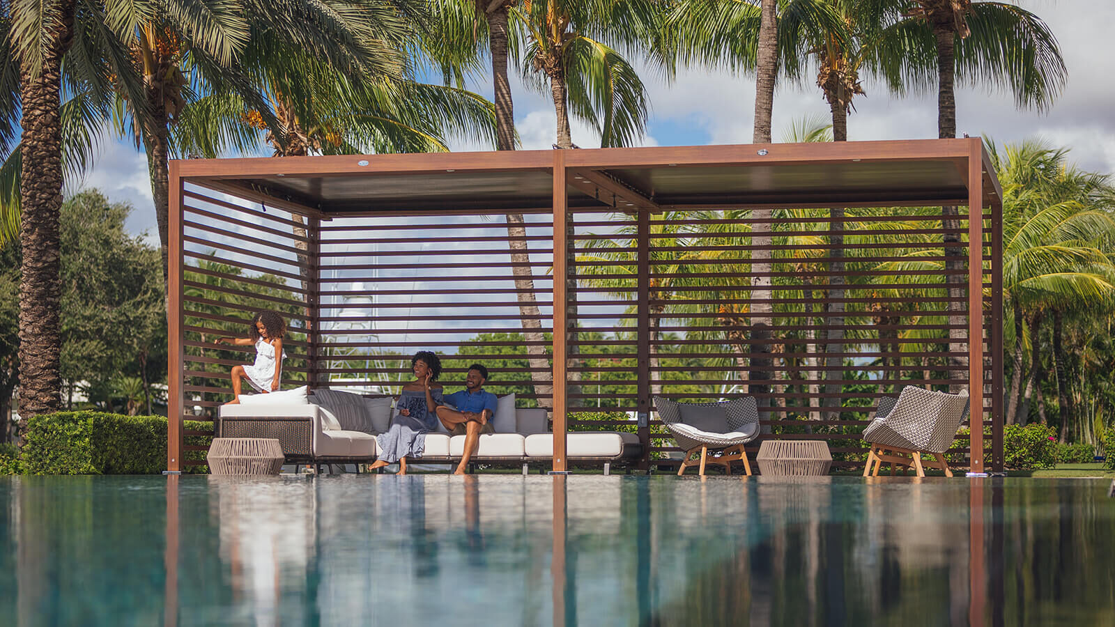 Family sitting on beige lounge seating under Tuuci's Equinox cabana with palm trees in the background