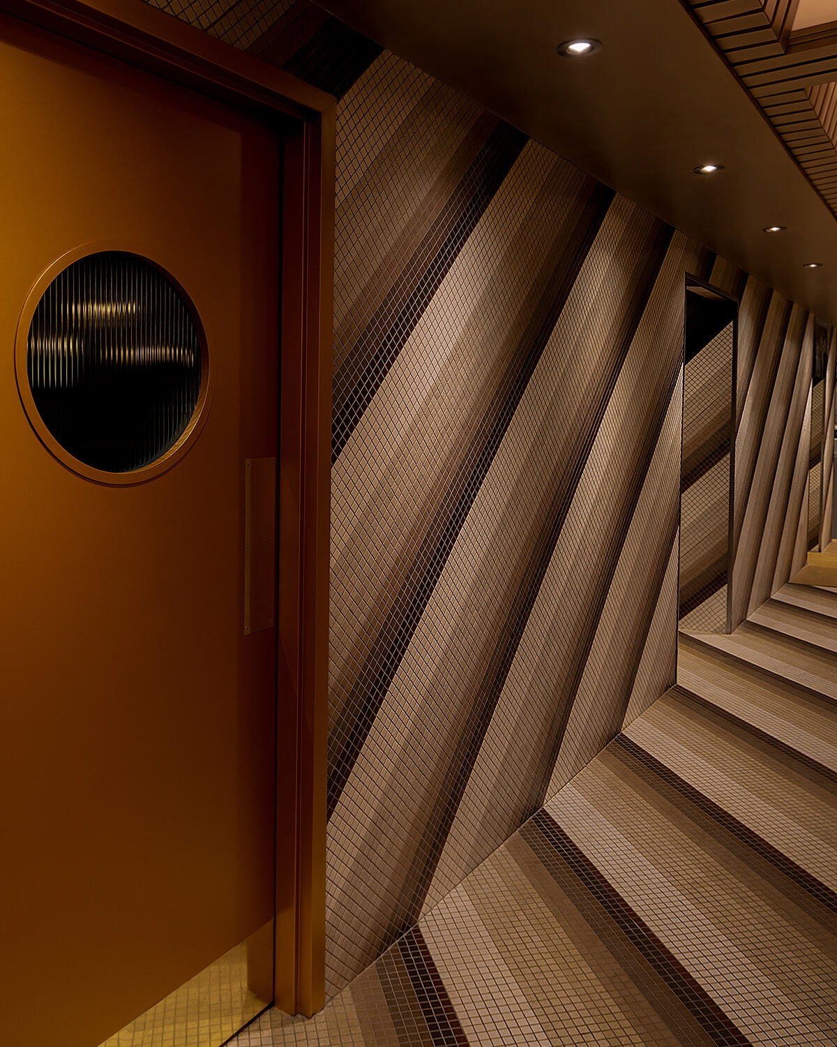 View of hallway showing door to office and diagonal tile pattern on floor and walls