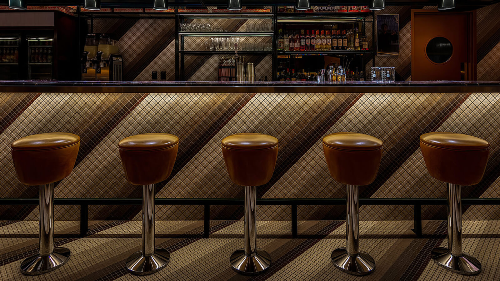 Photo of the bar, showing the brown vintage barstools and diagonal tile pattern