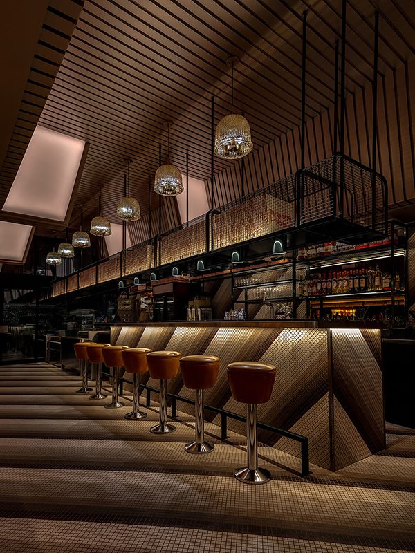 Photo of the bar, showing the diagonal tile pattern, brown vintage barstools, and antique light fixtures.
