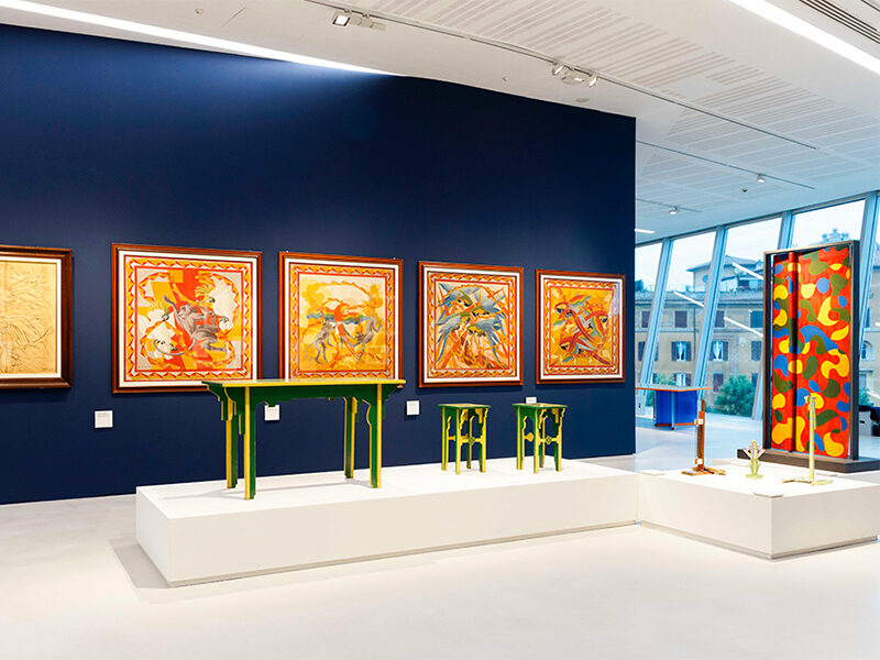 Green and yellow chairs/stools displayed in front of a blue wall with red and orange artwork